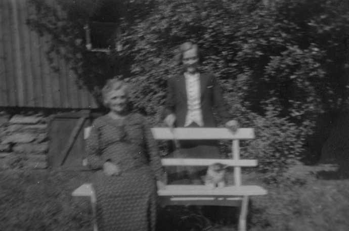 Bergine sitter på benken og bak står Carla og katten Knut.