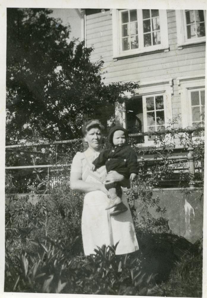 Solveig Olsen med barn foran huset